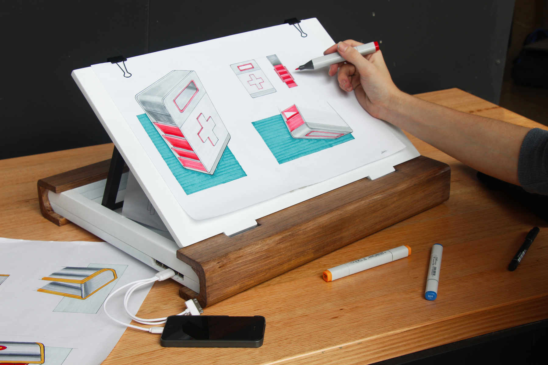 The drawing board provides an angled surface to draw on, while allowing the charging of electronic devices via a integrated power bank. Sketches and other materials can also be stored in the compartment underneath the board.